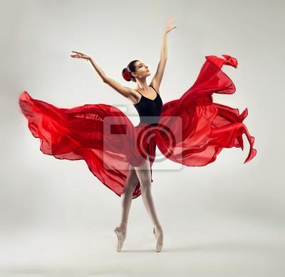 Obraz Balerina. Młoda, zgrabna kobieta baletnica, ubrana w profesjonalny strój, buty i czerwona spódnica w stanie nieważkości demonstruje umiejętność tańca. Piękno klasycznego tańca baletowego.
