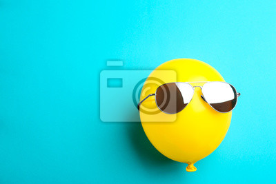 Obraz Balloon with sunglasses on blue background, top view. Space for text