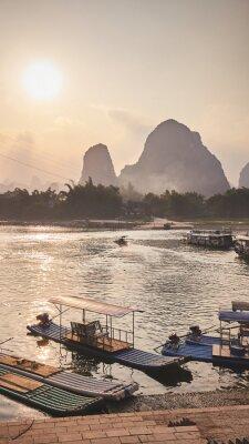 Bamboo rafts at Li River bank in Xingping at sunset, color toning applied, China.