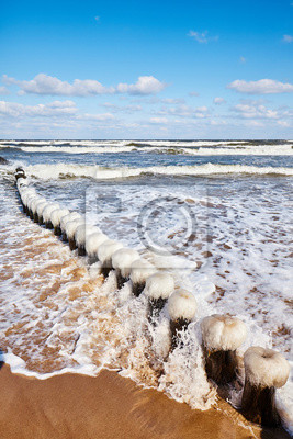 Beach with an icy wooden breakwater.