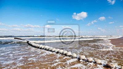 Beach with an icy wooden breakwater on a sunny day.