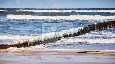 Beach with icy wooden breakwater on a sunny day.
