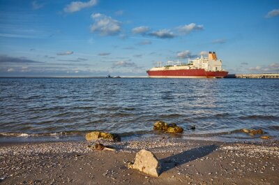 Beach with LNG tanker in distance at sunset.