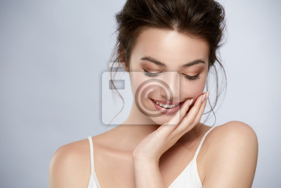Obraz beautifuk girl with golden make-up and in white t-shirt touching cheek and smiling