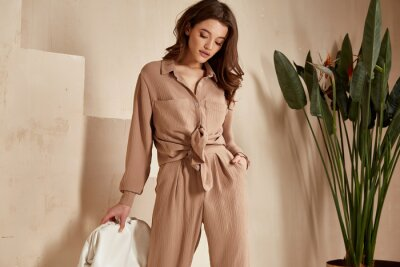 Obraz Beautiful brunette woman natural makeup wear fashion clothes casual dress code office style total beige blouse and pants suit, romantic date business meeting accessory bag interior stairs flowerpot.