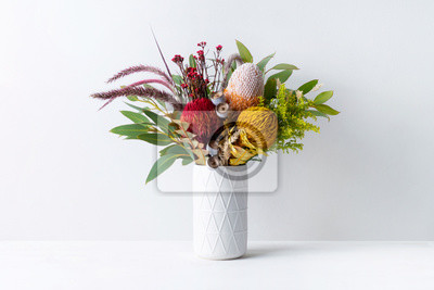 Obraz Beautiful floral arrangement of mostly Australian native banksias, eucalyptus leaves and gum nuts, fountain grass and dried kangaroo grass, in a white vase on a white table with a white background.