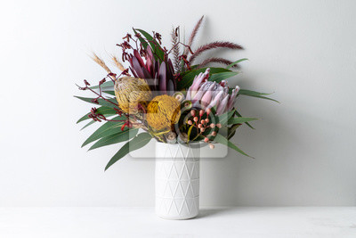 Obraz Beautiful floral arrangement of mostly Australian native flowers in a vase, including protea, banksia, kangaroo paw eucalyptus leaves and gum nuts on a white table with a white background.