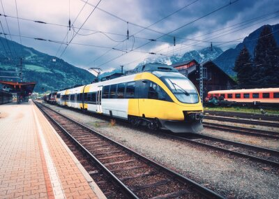 Beautiful high speed train on the railway station in mountains at sunset in autumn Yellow modern commuter train on the railway platform. Industrial landscape with railroad. Passenger transportation