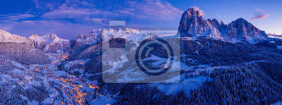 Obraz Beautiful panoramic view of Dolomites mountains at dusk during winter time. Magical winter mountain purple sunset with a mountain ski resort village. Christmas time.