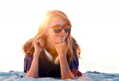 Beautiful redhead girl with headphones at beach sand.