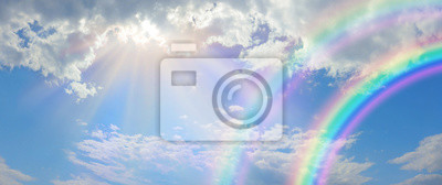 Obraz Beautiful vibrant double rainbow Cloudscape Background - awesome blue sky with pretty clouds, bright sun shining down and a large double rainbow arcing across the right corner with copy space