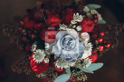 Obraz beautiful wedding bouquet with red roses and succulents. creative rustic bouquet for special occasion