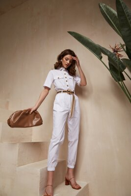 Obraz Beautiful woman fashion model brunette hair tanned skin wear white overalls button suit sandals high heels accessory bag clothes style journey safari summer collection plant flowerpot wall stairs.