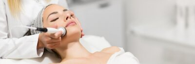 Obraz Beautiful woman in professional beauty salon during photo rejuvenation procedure