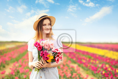 Obraz Beautiful young woman in tulip field on spring day