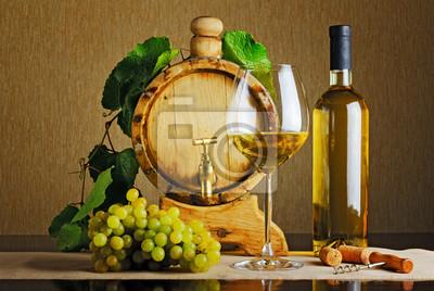 Beczki i butelki białego wina na stole.