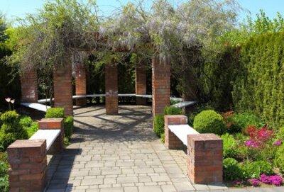 Obraz Bench in a decorative garden. Spring time.