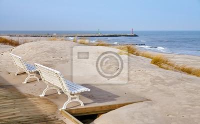 Benches along a  sea view wooden boardwalk, selective focus.