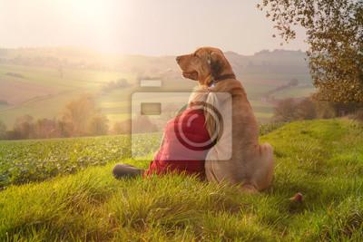 Obraz Beste Freunde - ein Kind lehnt sich an seinen Hund, einen Broholmer, an und beide genießen in der Natur den Sonnenuntergang an einem Herbsttag