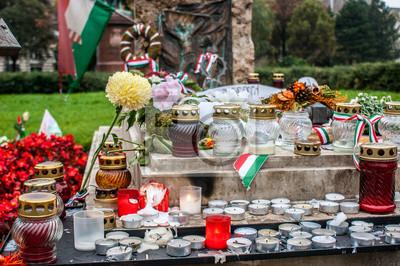 Białe świece, kwiaty w różnych kolorach i łuki z flagą Węgier w grobie jednej z ofiar rewolucji węgierskiej października 1956 roku w Budapeszcie