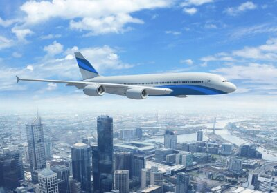 Obraz Biały samolot pasażerski lecący nad miastem