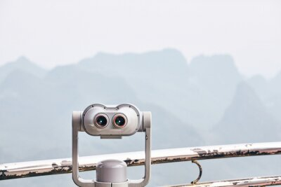Binoculars pointing at foggy mountain landscape of Karst formations in Guilin, selective focus, China.