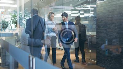 Obraz Biznesmen i interesu spaceru przez szklany korytarz, omawianie pracy i przy użyciu komputera typu Tablet. Zajęty korporacyjny budynek biurowy z wieloma pracownikami.