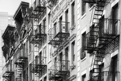 Black and white picture of Manhattan old residential buildings with fire escapes, New York City, USA.