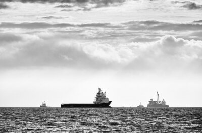 Black and white picture of ships silhouettes on the horizon at sunset.