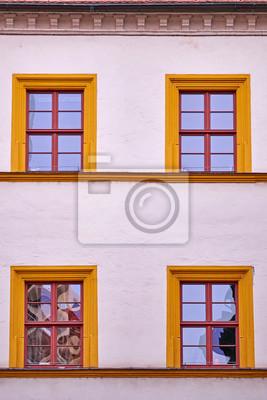 Obraz Blado Biala Fasada Budynku Z Pomaranczowymi Ramkami Okien Na