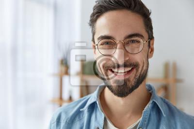Obraz Bliska strzał wesoły zadowolony atrakcyjny mężczyzna z zarostem, ma szeroki uśmiech, nosi okrągłe okulary, raduje się powodzeniem w pracy, stoi przed przytulnym wnętrzem. Modny projektant cieszy się p