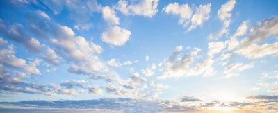 Obraz Blue sky clouds background. Beautiful landscape with clouds and orange sun on sky