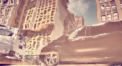 Blurred and distorted view of a car in New York City reflected in puddle, color toning applied, USA.