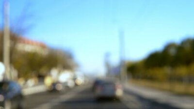 Obraz blurred background. Cars drive along the highway on a city bypass on a clear summer day. copy space. blue sky
