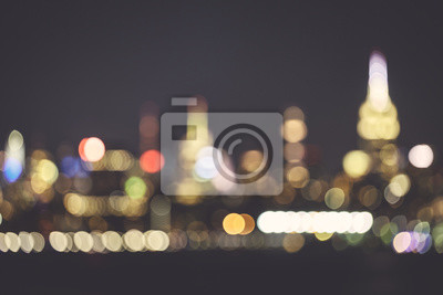 Blurred New York City skyline at night, color toned urban background, USA.