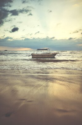 Boat at a tropical beach at sunset, color toning applied.