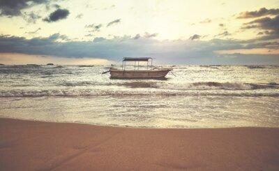Boat at a tropical beach at sunset, color toning applied, Sri Lanka.