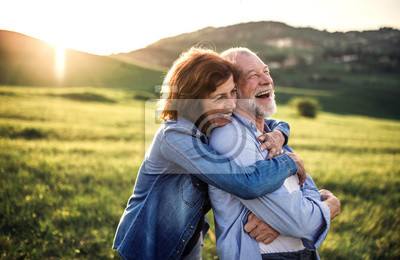 Obraz Boczny widok starszy pary przytulenie outside w wiosny naturze przy zmierzchem.