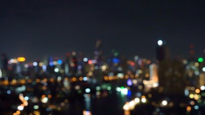Obraz Bokeh background of skyscraper buildings in city with lights, Blurry photo at night time. Cityscape