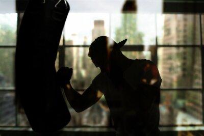 Obraz Bokser uderza w worek treningowy przed oknem, treningu