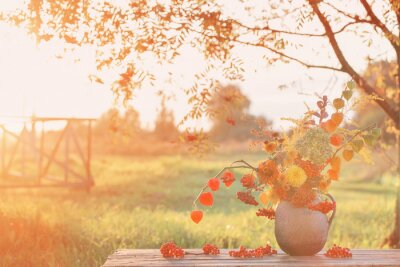 Obraz bouquet autumn flowers in rustic jug on wooden table outdoor at sunset