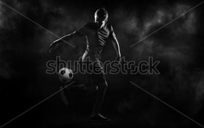 Obraz bright soccer playerl on the black background