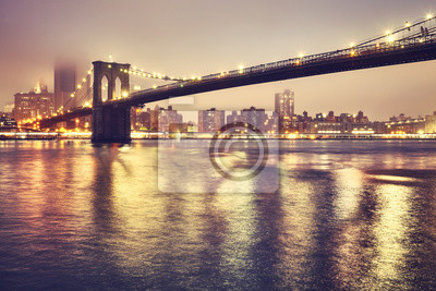 Brooklyn Bridge and the Manhattan on a foggy night, color toned picture, New York City, USA..