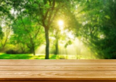 Obraz Brown wood table in green blur nature background of trees and grass in the park with empty copy space on the table for product display mockup. Fresh spring and natural product concept.