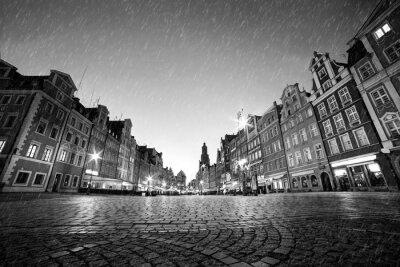 Brukowiec zabytkowego Starego Miasta w deszczu w nocy. Wrocław, Polska. Czarny i biały