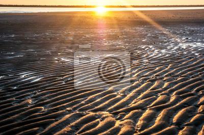 Bruzdy na plaży o zachodzie słońca w tle