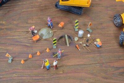 Budowa zabawki / Widok budowie mini zabawka pracownika na tle drewna.