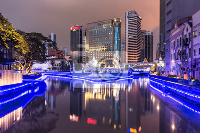 Budynki biurowe odbijają się w wodzie rzeki Klang przed meczetem Jamek w sercu Kuala Lumpur w Malezji.