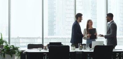 Obraz Businesspeople talking in office, standing against window