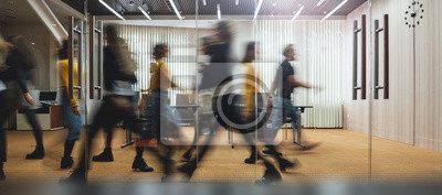Obraz Businesspeople walking at modern office. Group of business employees at coworking center. Motion blur. Concept work process. Wide image